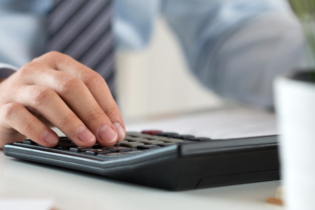 Close up of male accountant or banker calculating or checking balance