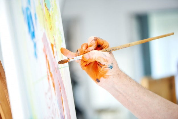 Close up of male artist hand, holding brush and painting rich orange paint in painter studio.