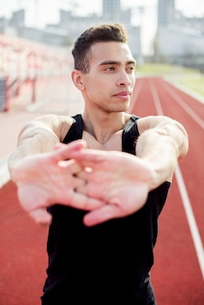 Close-up of a male athlete warming before running on running track Free Photo