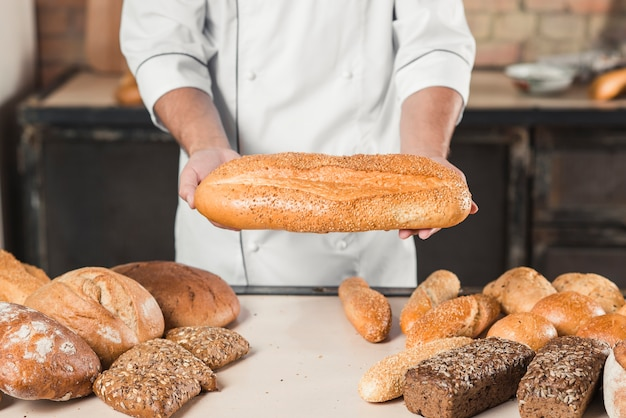 Close-up of male baker hands holding fresh bread