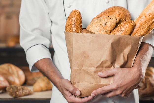 Close-up of male baker's hand holding baked bread in an paper bag