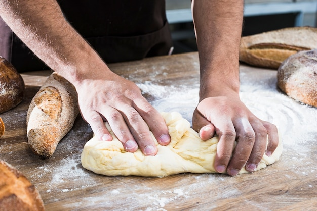 Close-up of a male baker's hand kneading the dough on table