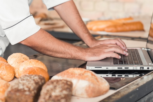 Close-up of male baker's hand using laptop on kitchen worktop with breads