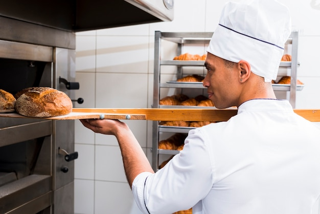 Close-up of male baker in uniform taking out with shovel freshly baked bread from the oven