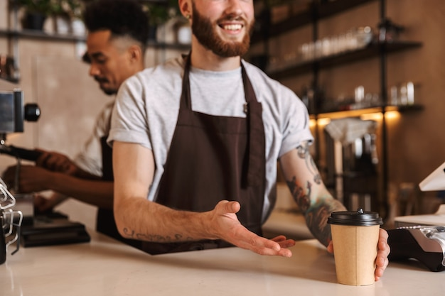 Close up of a male barista giving the order at the cafe counter