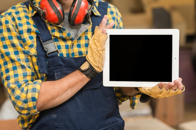 Close-up of a male carpenter showing digital tablet in his hand