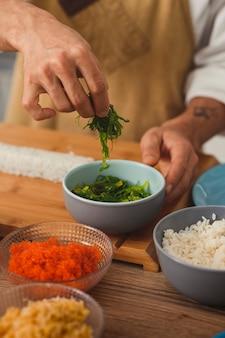 클로즈업 남성 요리사 손은 스시 롤 음식 배달 온라인 서비스 배경에 재료를 추가합니다