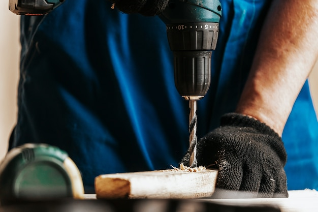 Close-up of a male construction worker in a black dirty construction overall closes a screw with a black modern screwdriver in a wooden block in the workshop