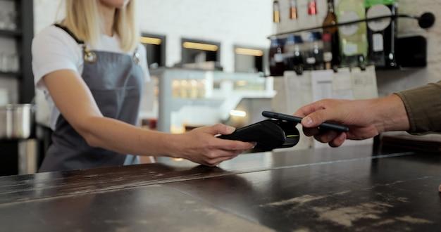 Крупный план мужчина-клиент платит бариста с помощью технологии бесконтактных платежей nfc на смартфоне