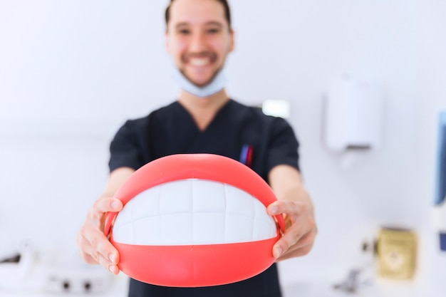 Close-up of male dentist showing teeth model in front of camera