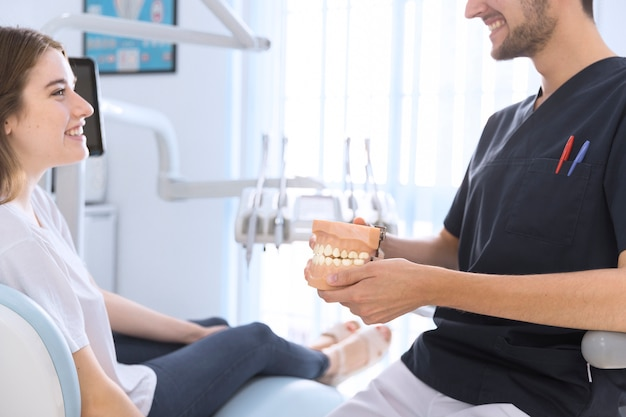 Close-up of a male dentist showing teeth model to patient