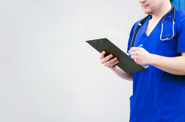 Close-up of a male doctor examining the clipboard with pen isolated against grey background