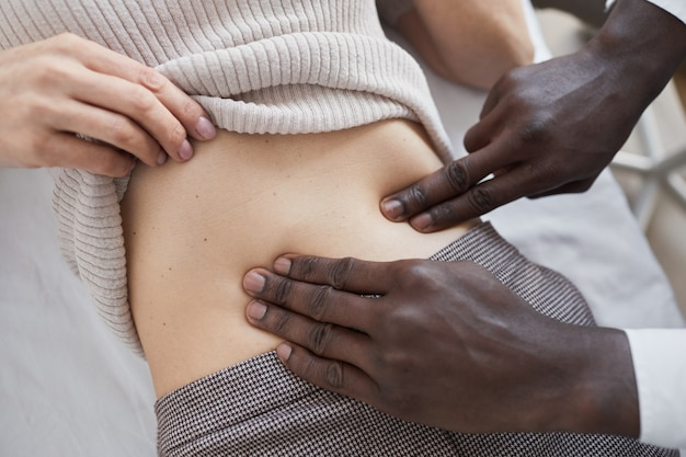 Close-up of male doctor holding medical examination of the woman's stomach