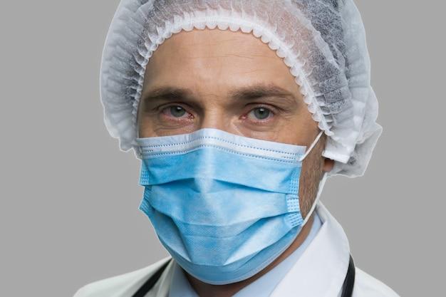 フェイスマスクで男性医師をクローズアップ。灰色の背景にカメラを見て保護マスクと帽子の自信を持って男性医師。