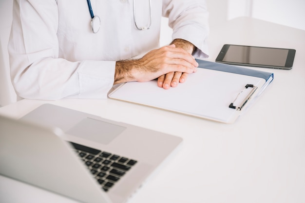 Close-up of a male doctor's hand on clipboard with laptop on desk