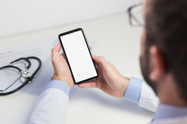 Close-up of a male doctor using mobile phone with white screen display