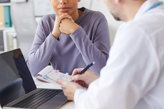 Close-up of male doctor writing a prescription to his patient at the table at hospital