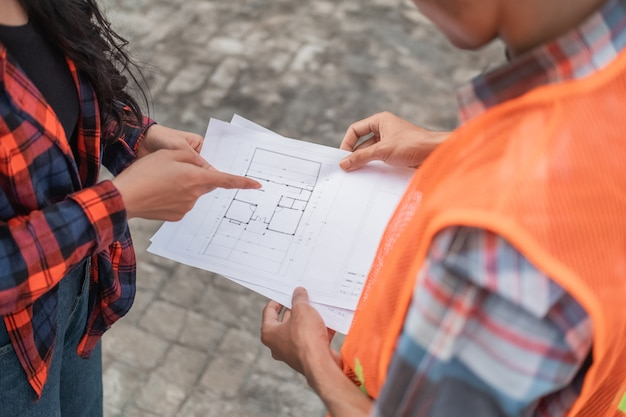 Close up of male and female asian contractors holding the building site plan