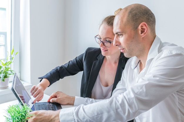Close-up of male and female businesspeople working on laptop at workplace
