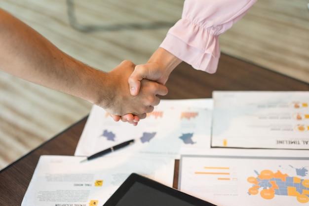 Close-up di mani maschili e femminile in stretta di mano sui documenti.