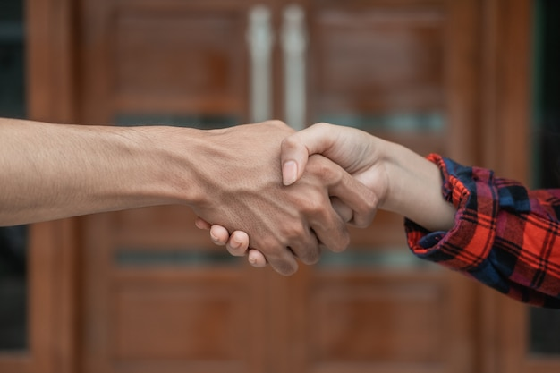 Close up of male and female hands shaking hands against the background of the door of the house