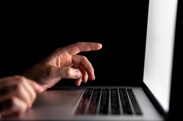 クローズアップ、男性の指が暗闇の中でノートパソコンの画面を指しています。