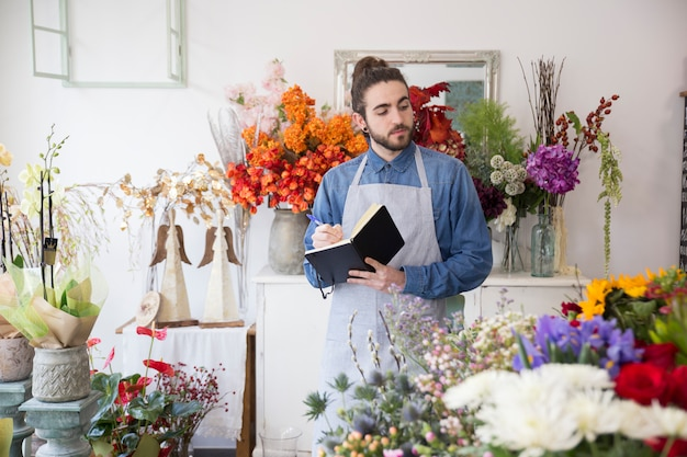 Close-up of a male florist looking at flower bouquet writing in the diary with pen