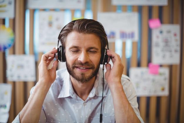 Close-up of male graphic designer listening music on headphone