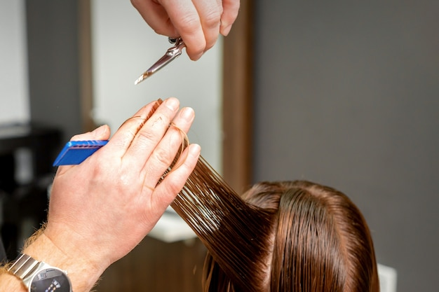 Close up of male hairdresser's hands cuts female hair in a hair salon. selective focus