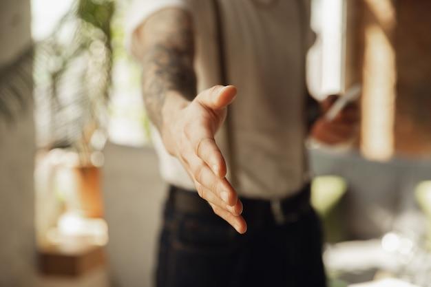 Primo piano della mano maschile che saluta, accogliendo qualcuno.