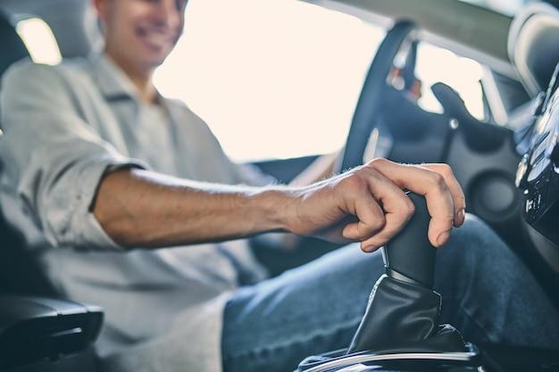 Крупным планом мужская рука, держащая коробку передач перед покупкой нового автомобиля в автосалоне