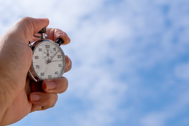 Close-up of a male hand holding an analog stopwatch over blue background. time management concept.