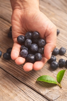 Close-up male hand holding a handful of blueberries on a wooden background with leaves