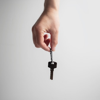 Close-up of male hand holding a house key on white.