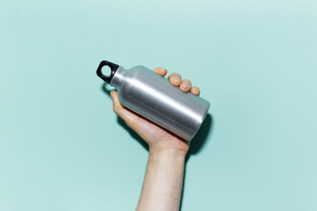 Close-up of male hand holding reusable, aluminum thermo bottle for water, on studio background of cyan, aqua menthe color. zero waste. plastic free.