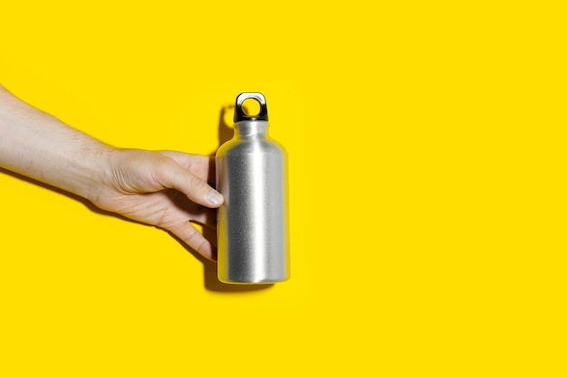 Close-up of male hand holding reusable, aluminum thermo bottle for water, on studio background of yellow color with copy space. zero waste. plastic free.