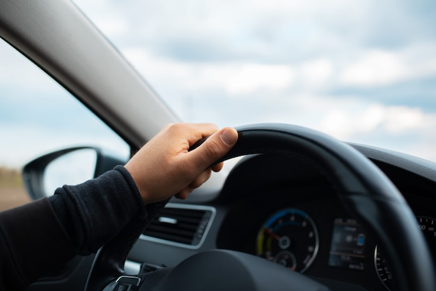 Close-up of male hand holding steering wheel