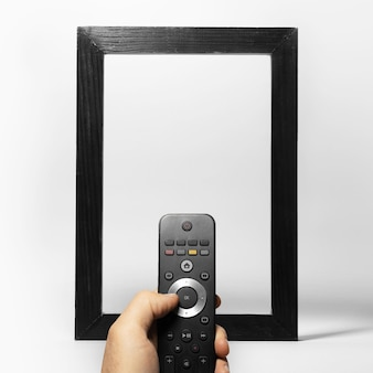 Close-up of male hand holding tv remote against black empty frame