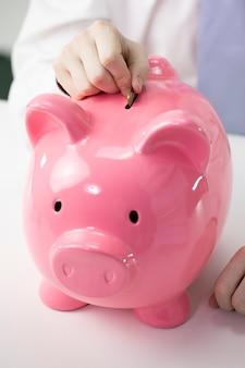 Закройте вверх по мужской руке кладя монетку к розовой копилке на белый стол, инвестируйте концепцию