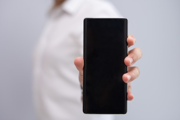 Close-up of male hand showing new model of smartphone