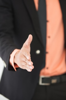 Close-up of male hand stretched for handshake