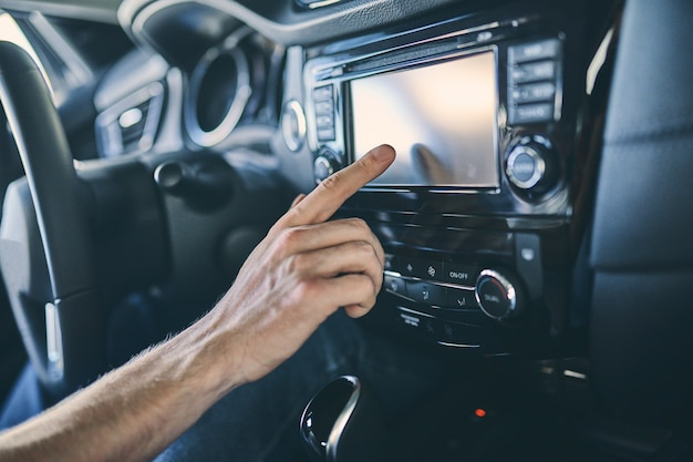 Close up male hand touch control panel before purchasing a new automobile in showroom