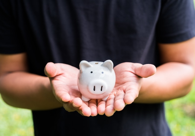 Close up male hands holding piggy bank.