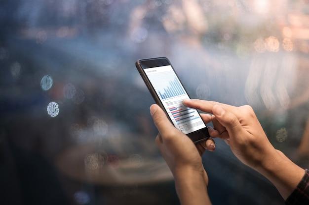 夜の街でグラフチャートでスマートフォンを持っている男性の手を閉じる