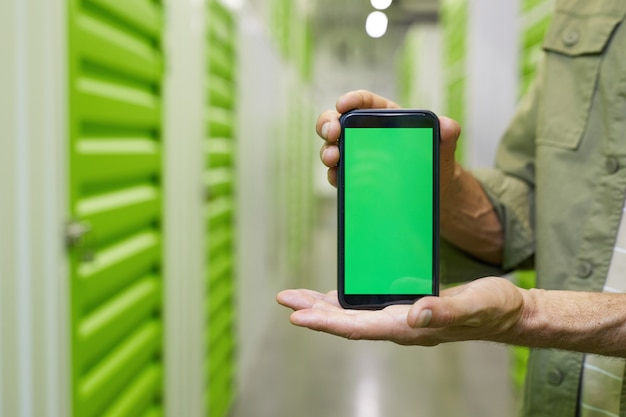 Close up of male hands holding smartphone with green screen against self storage facility surface, copy space