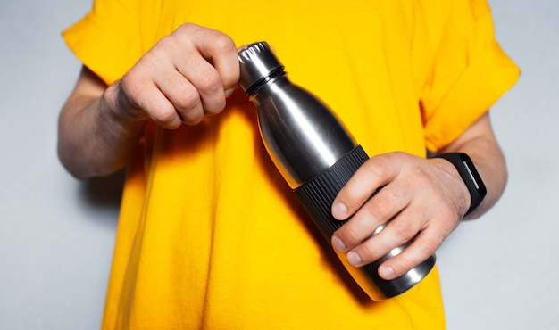 Close-up of male hands holding steel thermo water bottle.