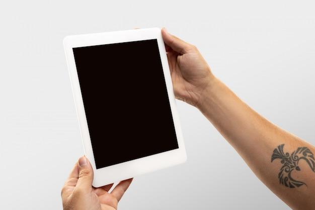 世界中の人気のあるスポーツの試合や選手権のオンライン視聴中に空白の画面でタブレットを保持している男性の手を閉じます。