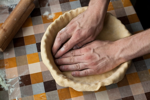 Close up of male hands kneading dough on a surface in cell