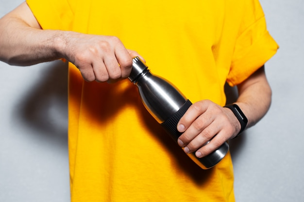 Close-up of male hands opens reusable metal bottle