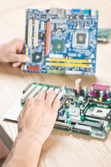 Close-up of male hands practicing to repair motherboard on wooden table